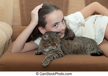 girl with a cat on a sofa - portrait of the girl with a cat...