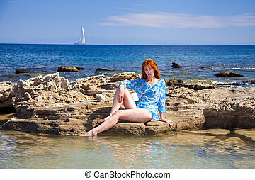 Greece. Rhodes. The young beautiful woman on seacoast.