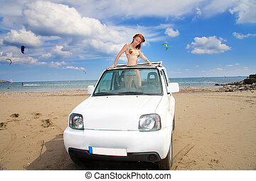 The young beautiful woman in the car on seacoast.