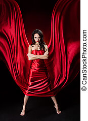 Mysterious  woman in red waving silk dress over black background.