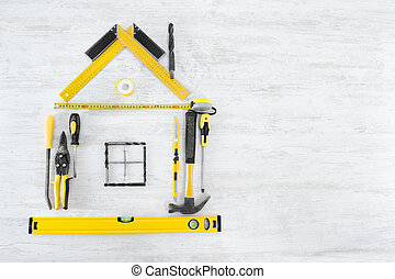 Tools in the shape of house over wooden background. Home improvement concept.