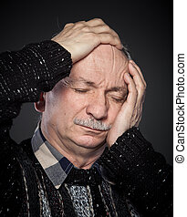 headache - an older man suffering from a headache