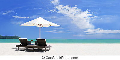 panoramic view ow the tropical beach with umbrella and two...
