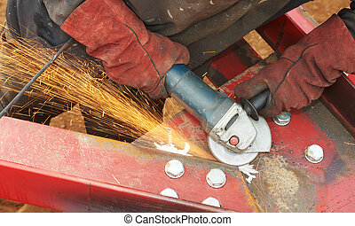 grinding machine works with sparks - Builder hands in safety...
