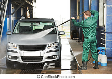 worker cleaning car with pressured water - manual car...