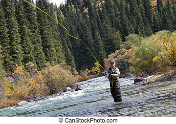 Fisherman fly fishing - fly fishing angler makes cast while...