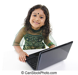 Little IT user - Little Indian girl using a laptop on table,...