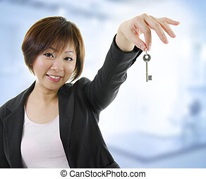 New property - Mid adult Asian woman arms out holding a new...