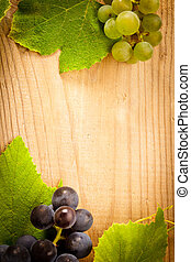 Grape on wooden table - Different grapes with green leaves...