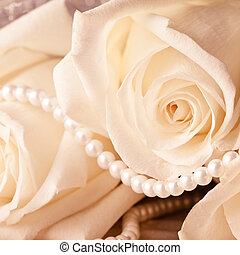 Pearl beads and cream rose on the silk background