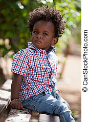 Outdoor portrait of a black baby sited on a bench - Outdoor...