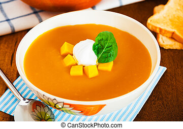 Pumpkin soup with cream in a bowl with painted flower and...