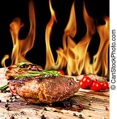 Steaks - Grilled beef steaks with flames on background