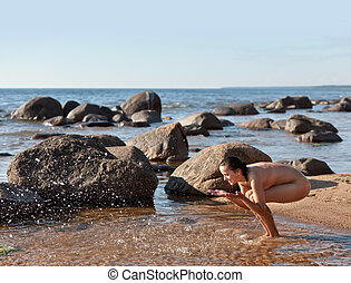Nude woman playing with water