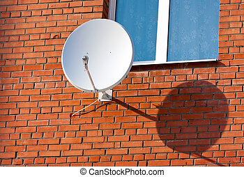 Satellite Dish mounted on  brick wall.
