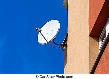 Satellite Dish mounted on  brick wall against blue sky background