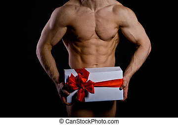 handsome muscular young man holding a present