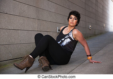 beautiful young woman, looking to camera, sitting on the floor, with a wall from background, outside