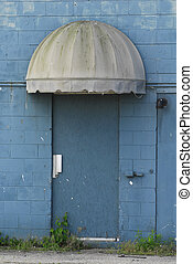 Blue Door - A blue door under a grungy canopy on a cement...