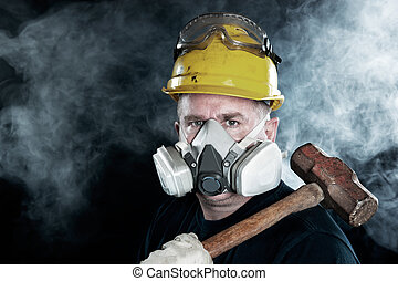 Worker in smoke - A rescue worker wears a respirator in a...