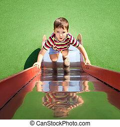 boy climbing up a slide - Cute young boy climbing up a slide...