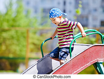 boy playing on slide - Cute boy in bandana playing on slide