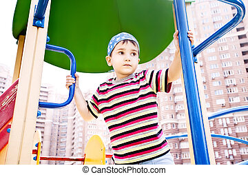 Young boy in bandana on playground thoughtfully looking into...