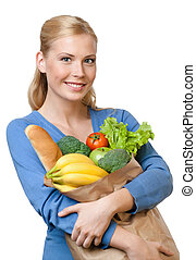 Young woman with a bag full of healthy food