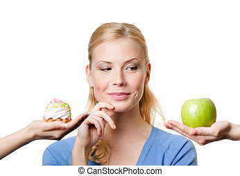 Young woman makes a choice between cake and apple -...