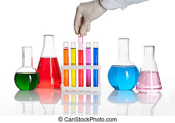 Set of chemical flasks and test tubes with a hand holds one...