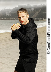 Young athlete boxer at beach - Beach portrait of an active...