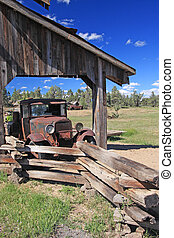 Old Farm Truck - Old rusty farming truck underneath a...