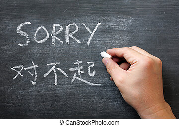 Sorry - word written on a smudged blackboard with a Chinese...