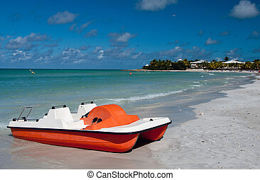 Pedal boat on a tropical beach - White red pedalo on the...