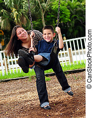 Mother pushing son on swing - Beautiful mother pushing her...