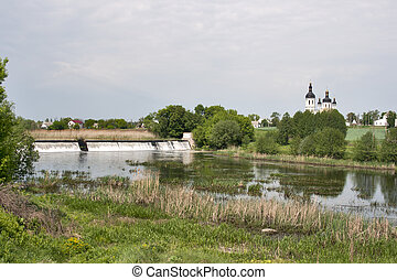 Country side landscape with dam, church and river Ros...