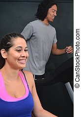 Woman and Man at Gym - Man running and woman at the gym