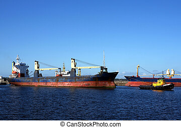 Towage - The tow drags the cargoship in harbour