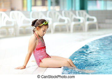 Child relaxing by swimming pool - Cute child with goggles...