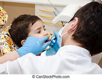 Boy in dentists office - Little boy healing his teeth in...
