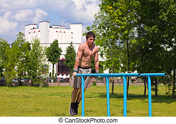 street workout - Teen doing gymnastics on the uneven bars at...