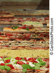 Different varieties of pizza displayed in a Pizzeria