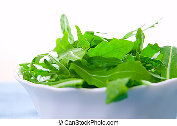Green rucola fresh salad in white bowl