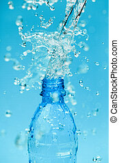 Mineral water - splash water from bottle on blue