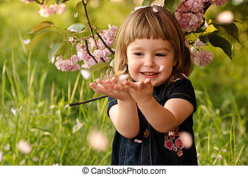 Little girl in garden, under the sakura tree. Spring petal's...