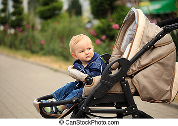 Toddler in baby carriage - Sweet blonde toddler are sitting...