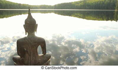 Buddha at the Lake. - Sculpture of a Buddha looking out over...