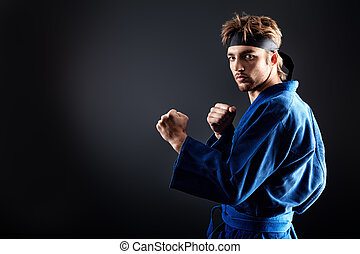 karate man - Martial arts fighter posing at studio.