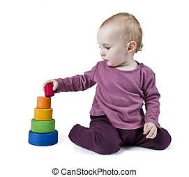 young child playing with colorful toy blocks