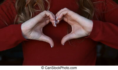 Heart hands - Young woman holds her hands in shape of a...